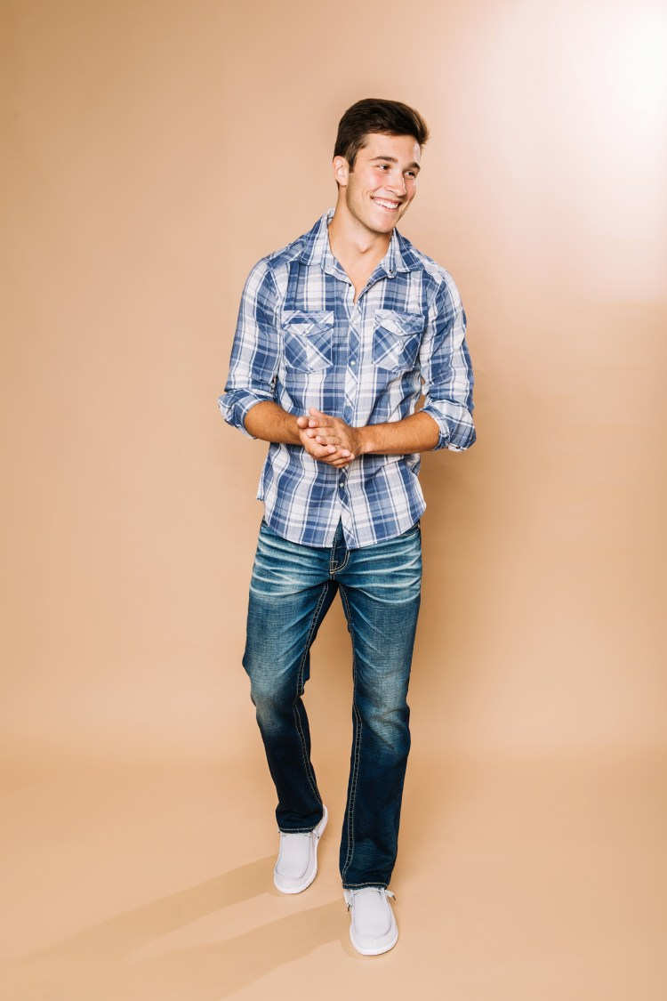 Male model wearing blue plaid BKE button down with BKE denim and Hey Dude casual shoe.