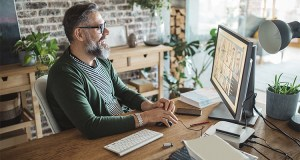 Man sitting at desk looks at computer monitor