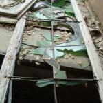 Durch Vandalismus zerstörtes historisches Glasfenster.