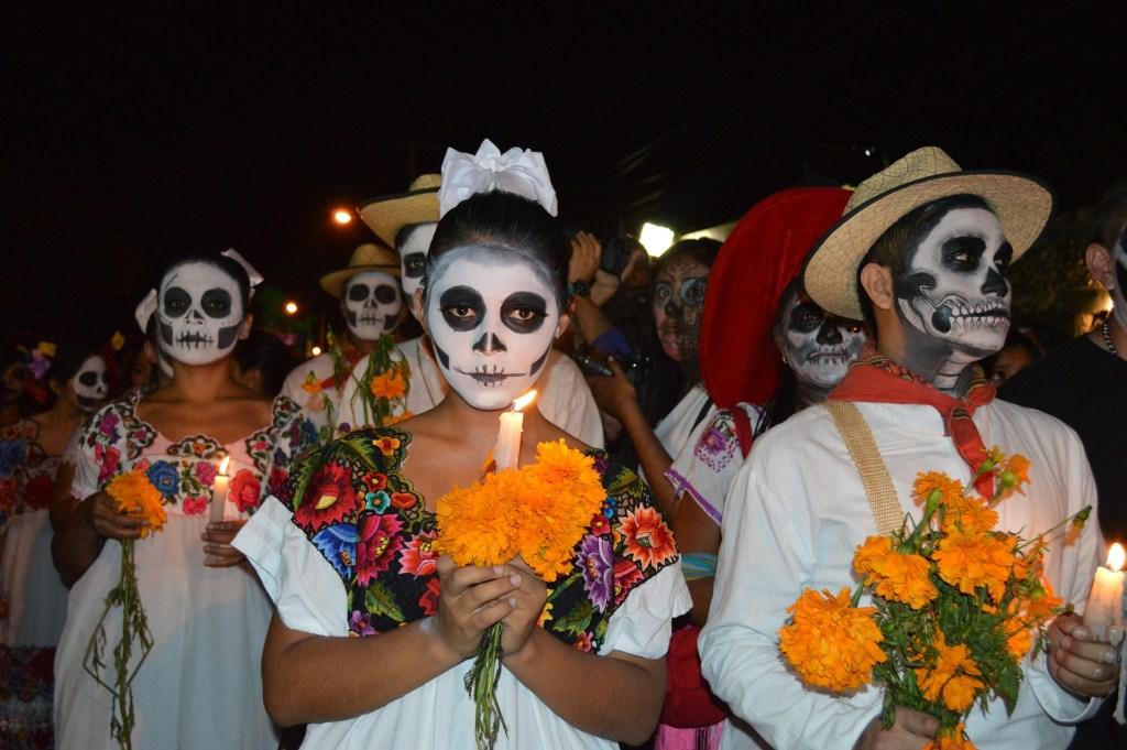 El día de los muertos group walks with candles
