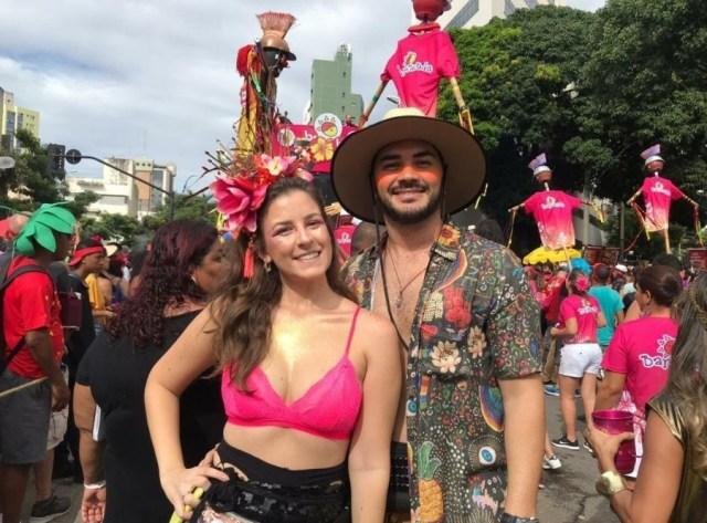 Casal aproveita Carnaval de BH ao som da Bartucada. Ao fundo da foto aparecem foliões.