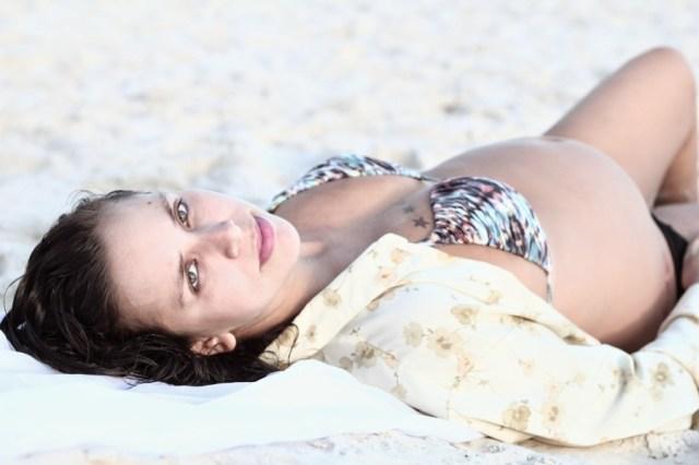 Mulher, Isabelle Castillo, visivelmente grávida na praia do Arpoador