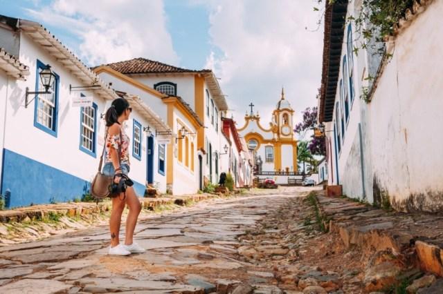 Na foto esta uma mulher em uma ladeira de tiradentes. Um dos destinos para casais mais românticos do Brasil e ideal para o Dia dos Namorados