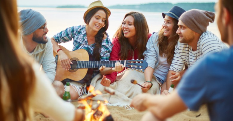 A Group Of Friends Singing Around A Campfire