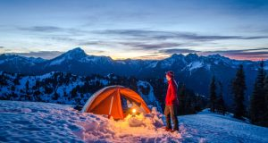 A Man Standing By His Glowing Tent In The Snowy Mountains