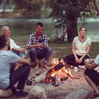 A Group Of Friends Playing Fun Games Around A Campfire
