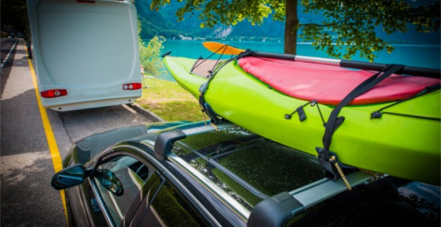 green kayak on top of an SUV behind an rv