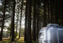 a camper trailer sits in a dark woods
