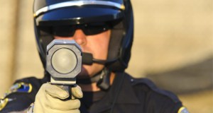 Police Officer With Speed Gun Clocking Cars and Trucks