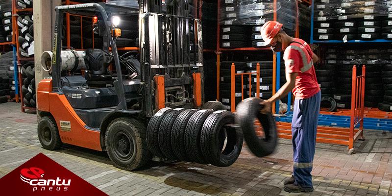 Operador colando pneus para o transporte