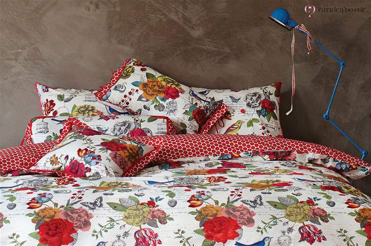 Cama de casal com travesseiros e colcha de estampa florida