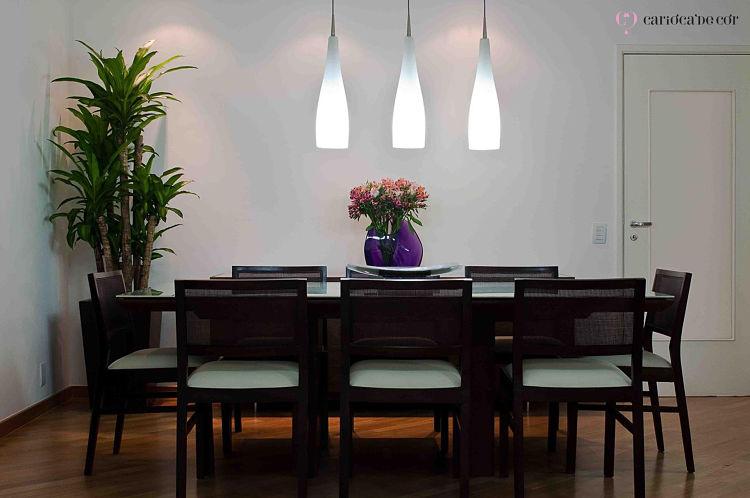 Sala de jantar iluminada, com mesa de oito lugares, retangular ao centro