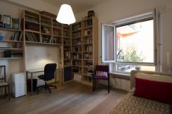 foto di una camera da letto singola, con libreria, scrivania, letto, poltroncina e finestra spalancata su un balcone