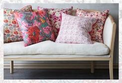Un divano con cuscini rivestiti con tessuto in stile liberty Intaglio su legno pieno.