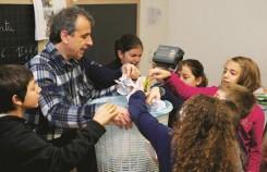 Il maestro Rossano Ercolini attorniato dai suoi alunni che ripongono la carta utilizzata nel cestino del riciclo
