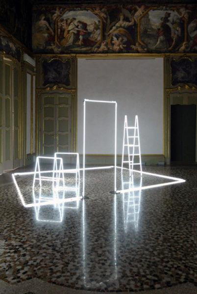 Una scala, due sedie, perimetro del pavimento e della porta sono realizzati tramite dei tubi al neo e collocati in una sala museale