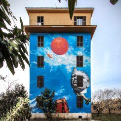 mural colorato sull'intera facciata della palazzina che rappresenta un cielo blu dove gravitano alcune figure surreali.
