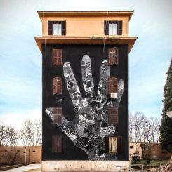 mural colorato sull'intera facciata della palazzina che rappresenta su sfondo nero una mano gigante sulla cui superfice vi sono motivi grafici in bianco