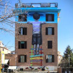 mural colorato sull'intera facciata della palazzina che rappresenta un bambino arrampicato su una scaletta colorata che con la testa sembra sfondare una superficie blu cielo