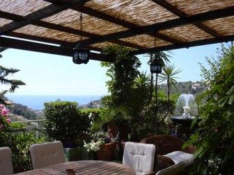 come arredare il terrazzo: tavolo e sedie con stuoia per riparare dal sole