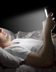 elettromagnetismo in casa: uomo sdraiato sul letto guarda il cellulare