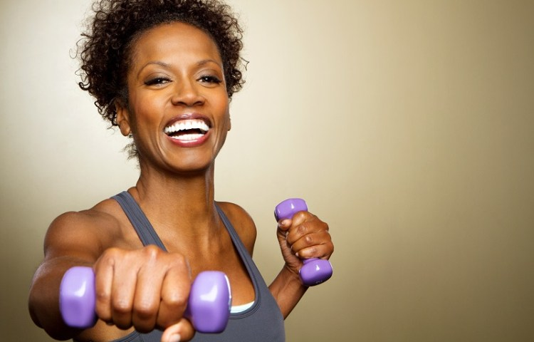 woman smiling holding weights