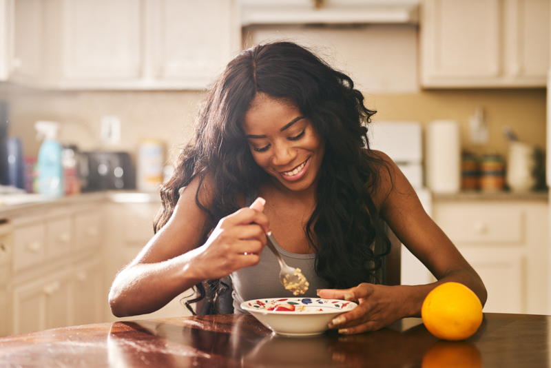girl smiling and eating her oatmeal