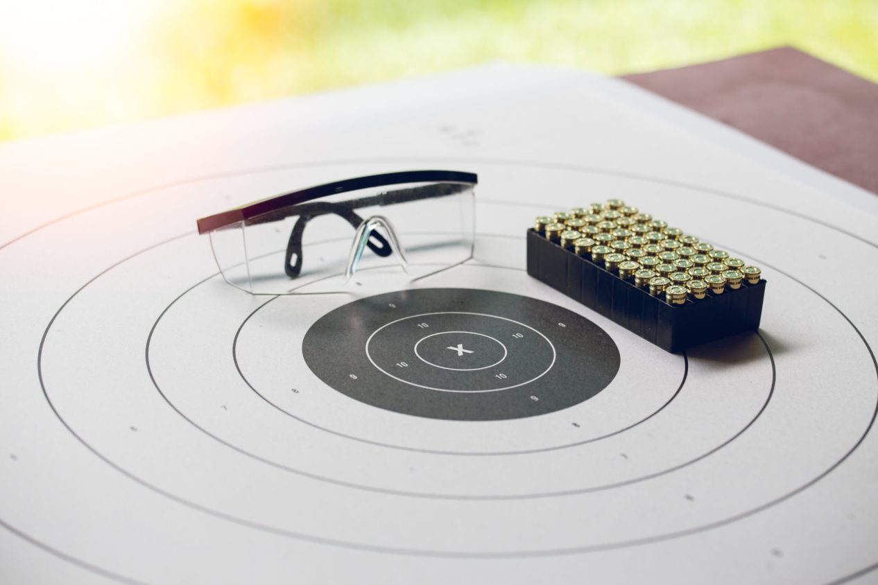 vintage paper shooting target with box of 9 mm bullet and protection glassess at shooting range with flare