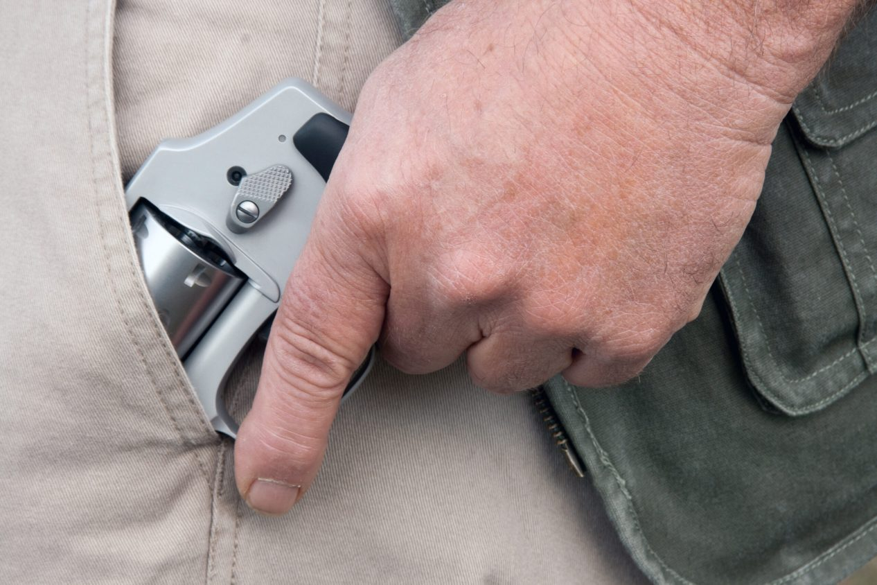 man drawing a concealed weapon from his pants pocket