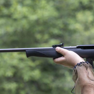 Someone aiming a 22 rifle