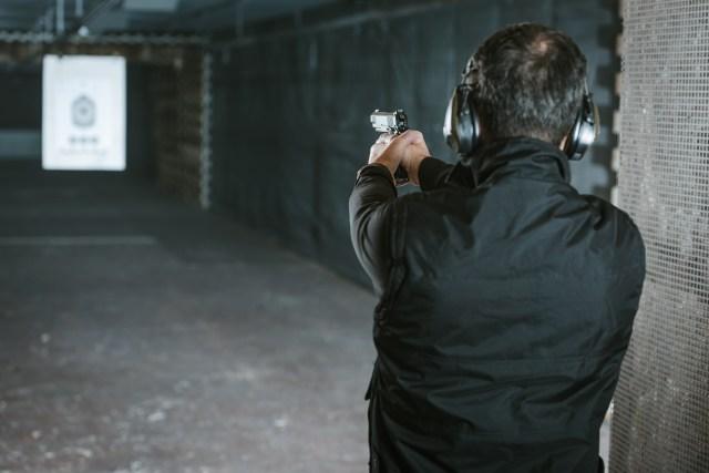 rear view of man aiming handguns at target in shooting range