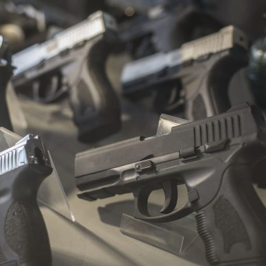 Black pistols behind the glass of a weapon store counter. Unusual view. Firearms, black pistols.
