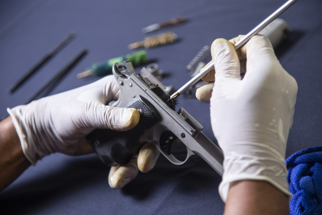 Gunsmith cleaning gun rifle and pistol assemble dismantle maintenance with brush clean handgun owner basics