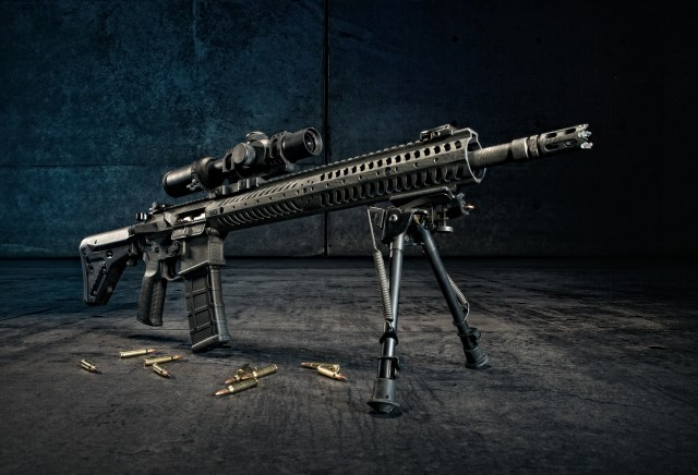AR-15 built for long-range shooting displayed on a bipod with a magazine inserted and shell casings below it.