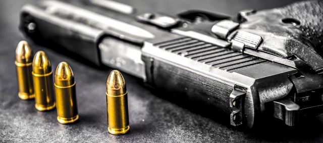 Bullets and handcuffs. Close-up of 9mm pistol. Gun and weapon with bullets amunition on black backround.
