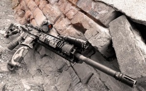digital camo AR-15 laying on some concrete bricks