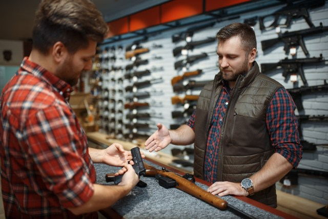 guns for beginners Man and owner choosing rifle and handgun in gun shop. Euqipment for hunters in weapon store, hunting and sport shooting hobby, security and selfdefence