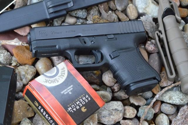 Closeup of Glock G29 pistol left with Federal ammunition box