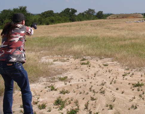Man in camo and jeans points his 1911 at a target about 300 yards away, across an expanse of grass and dirt