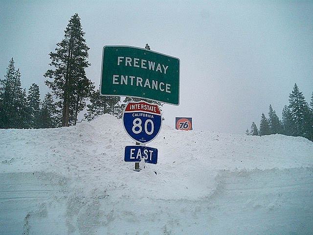 Picture shows a highway sign covered in snow.