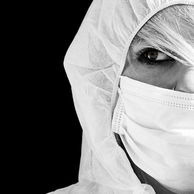 black and white image showing half a woman's face wearing a gas mask and decontaminate suit