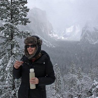 Picture shows a woman bundled up in a coat, sipping a beverage in the snow.