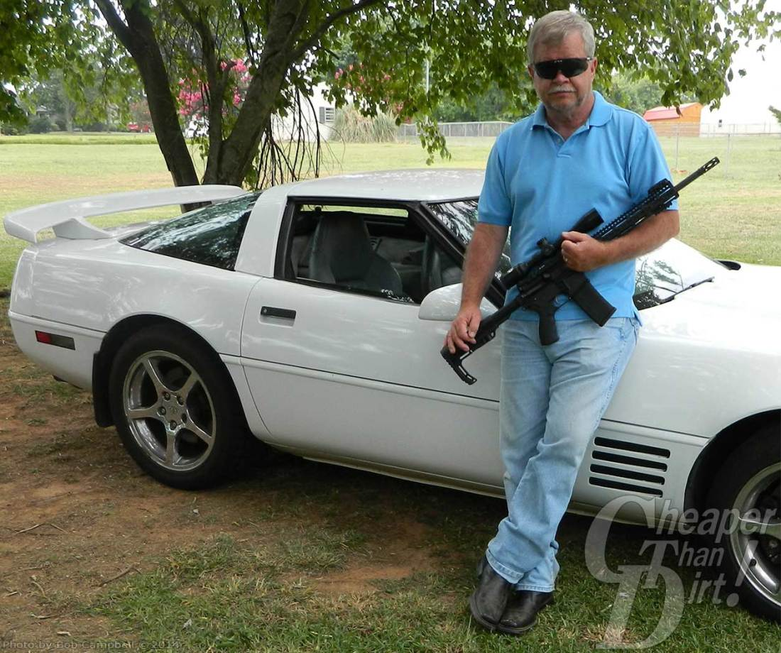 Picture shows a man holding an AR-15 rifle, leaning against a Corvette.
