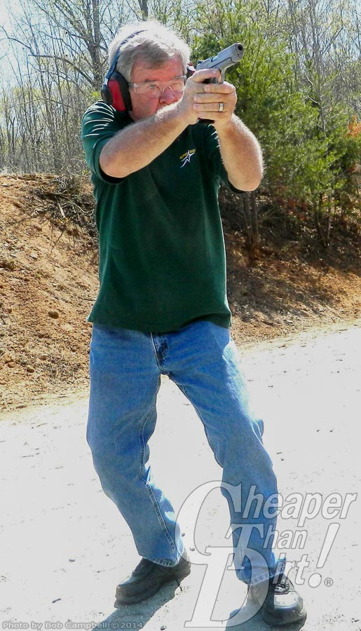 Gray haired man in green shirt, blue jeans and red ear protection practices his shooting skills with wooded area in the background.