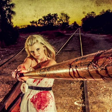 Image shows a woman dressed in a wedding dress with blood splatter on it, holding and swinging a bloody baseball bat