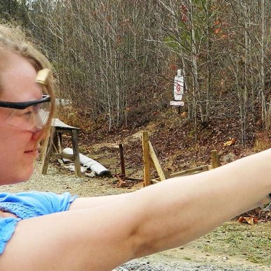 Blond woman in blue shirt shoots aluminum framed handgun