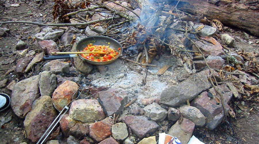 Picture shows a meal being prepared over an open campfire.
