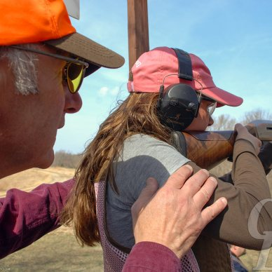 Man in orange ballcap stands behind a woman with long brown hair, pink ballcap and black ear protection teaching her to shoot at a target