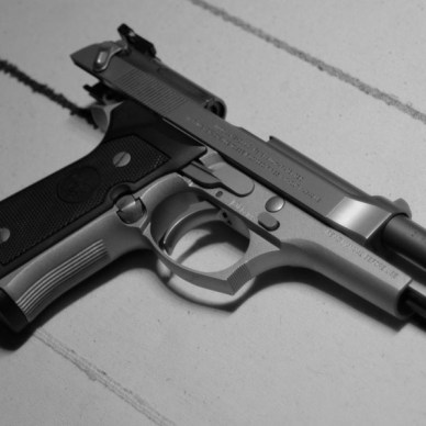 Picture shows a silver Beretta handgun with the slide locked back.