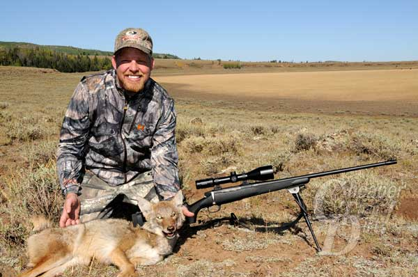 HUnter with a coyote and McMillian Legacy Rifle